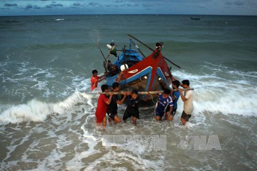 Kéo thuyền vào bãi sau một ngày đánh bắt ngoài khơi biển miền Trung. Ảnh: Tuấn Anh/TTXVN