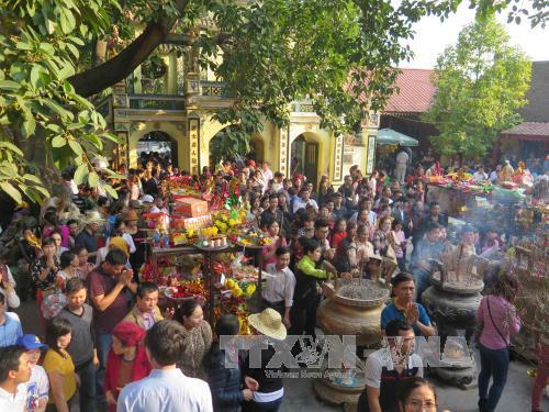 Du khách thập phương dâng lễ vật vào sân Đền Bà Chúa kho. Ảnh: Thanh Thương/TTXVN