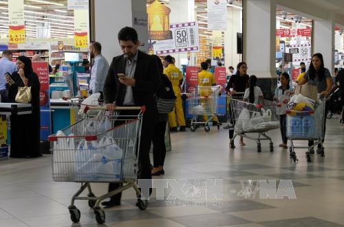 nguoi dan mua luong thuc, thuc pham tich tru tai mot sieu thi o doha, qatar, ngay 6/6. anh: thx/ttxvn
