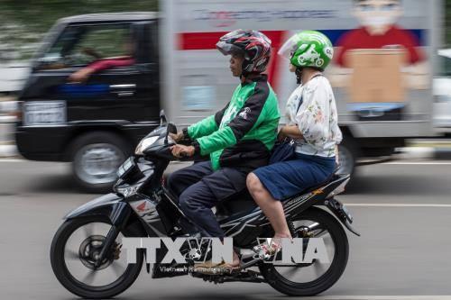 nguoi dan su dung dich vu di xe may cua hang go-jek tren duong pho jakarta, indonesia ngay 24/5. anh: afp/ttxvn