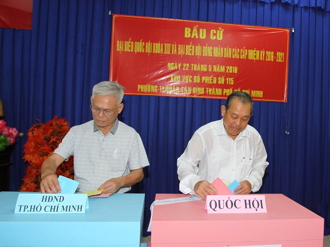 Đồng chí Trương Hòa Bình, Ủy viên Bộ chính trị, Phó Thủ tướng Chính phủ (phải) đến bỏ phiếu tại khu vực bỏ phiếu Trường tiểu học Nguyễn Văn Trỗi, Phường 11, quận Tân Bình, Thành phố Hồ Chí Minh.