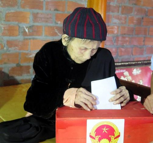 Các thành viên đơn vị bầu cử số 1, xã Tân Trào, huyện Sơn Dương (Tuyên Quang) mang hòm phiếu phụ đến tận nhà và hướng dẫn cử tri bỏ phiếu.