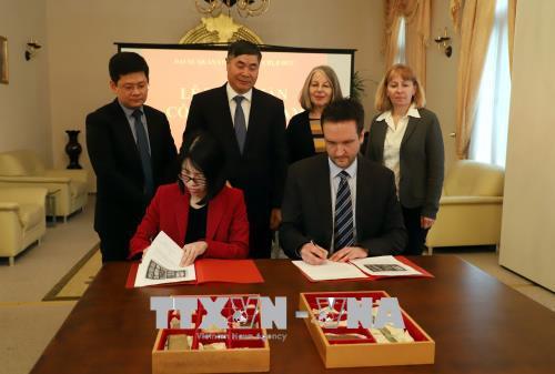 Bà Chu Thu Hằng, Bí thư thứ nhất thuộc Đại sứ Việt Nam tại Đức và Đại diện Cảnh sát bang Berlin ký biên bản bàn giao cổ vật. Ảnh: Phạm Thắng/PV TTXVN tại Đức