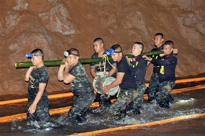 Lực lượng cứu hộ vận chuyển các thiết bị vào trong hang để nhanh chóng tháo nước ra ngoài. Ảnh: EPA