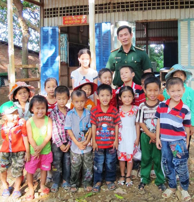 Thầy giáo Trần Bình Phục chụp ảnh cùng học sinh tại lớp học. Ảnh: Tiến Hưng