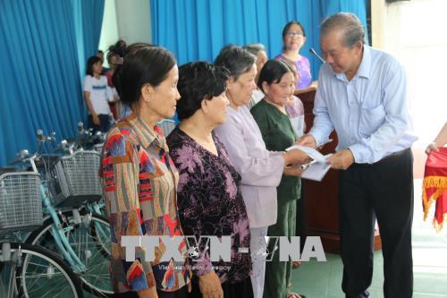 Đồng chí Trương Hòa Bình đến thăm và tặng quà các Mẹ Việt Nam anh hùng thị xã Cai Lậy và huyện Cai Lậy. Ảnh: Minh Trí /TTXVN